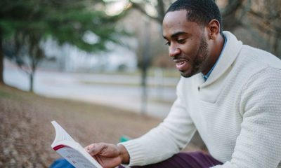 Man reading how to win friends and influence people at park