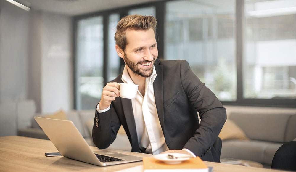Man drinking coffee in front of laptop confidently
