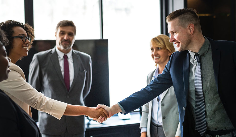 Man and woman shaking hands in front of coworkers