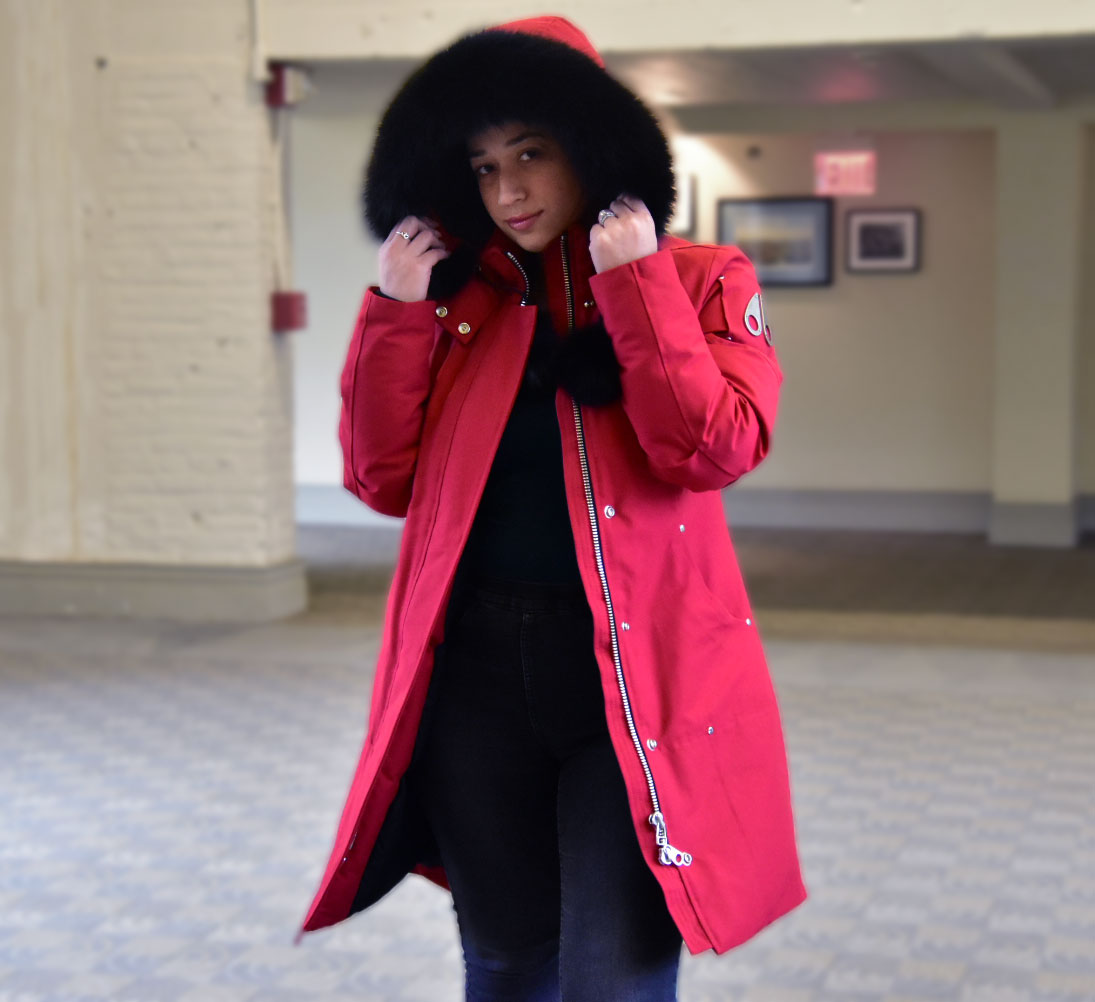 Model posing with Moose Knuckles Stirling Red Parka