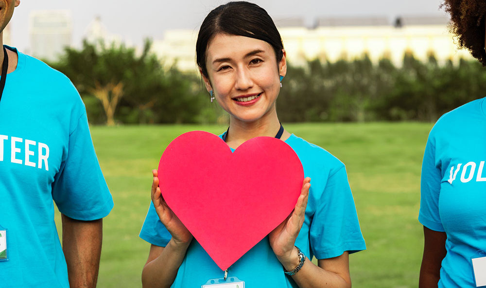 Asian woman holding up red heart cutout