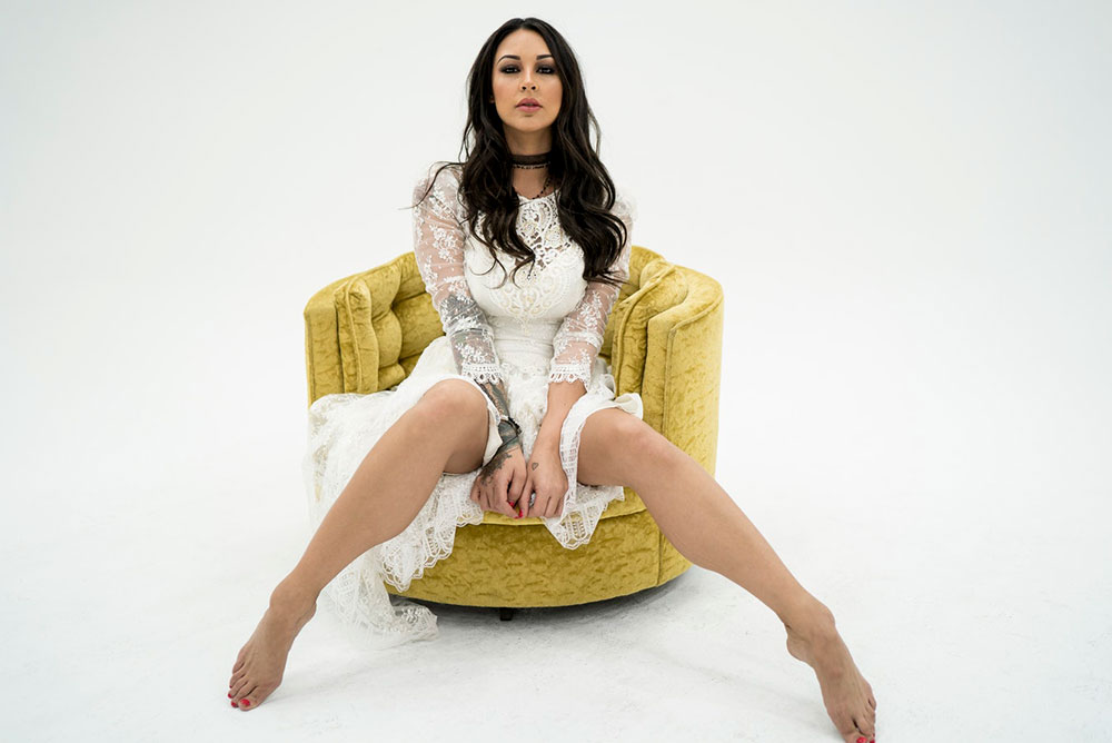 Attractive female entrepreneur in white dress sitting in yellow arm chair