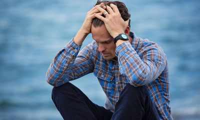 White man with plaid shirt sitting stressed out by ocean