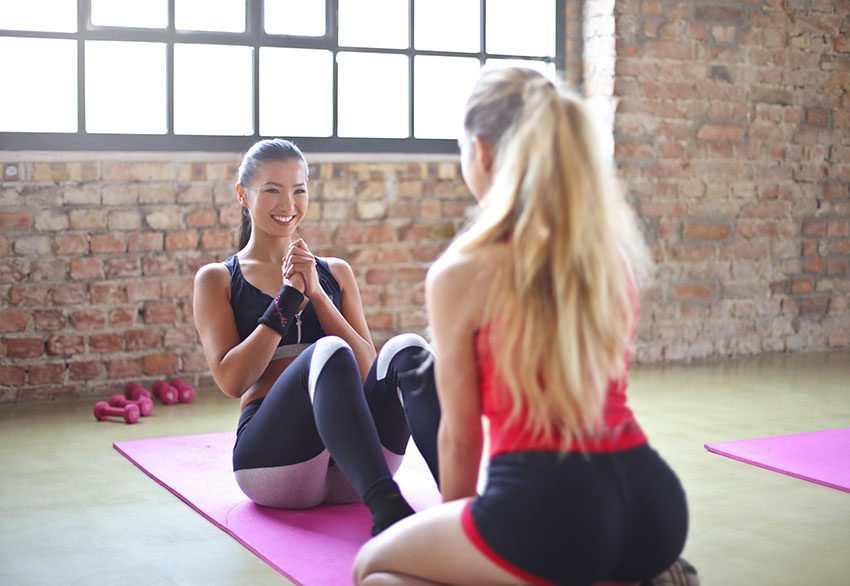 Two young women working out in the morning at the gym