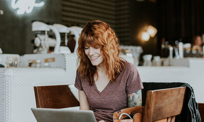 Red hair woman blogging at coffee shop