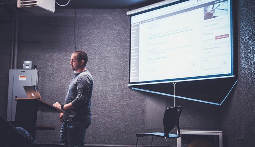 Speaker at an event showing slide presentation